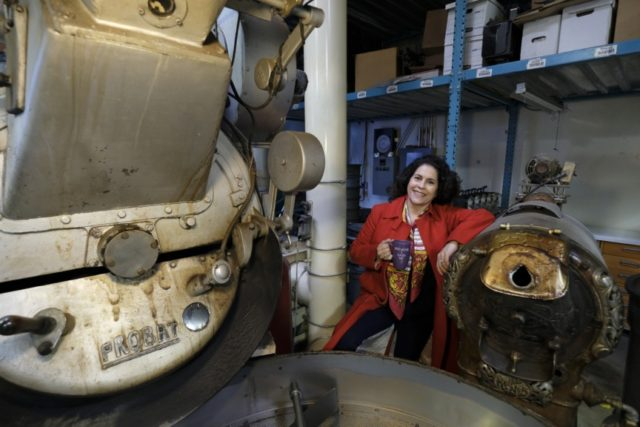 In this photo taken Wednesday, March 11, 2020, Renee Brown, vice-president of Wild Card Roasters, poses between a pair of coffee roasters at her roastery and cafe in San Rafael, Calif. As the coronavirus spreads, many small business owners are rethinking their strategies and adjusting the way they work. (AP …
