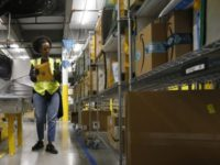 In this Dec. 17, 2019, file photo, Tahsha Sydnor stows packages into special containers after Amazon robots deliver separated packages by zip code at an Amazon warehouse facility in Goodyear, Ariz. On Monday, March 16, 2020, Amazon said that it needs to hire 100,000 people across the U.S. to keep …