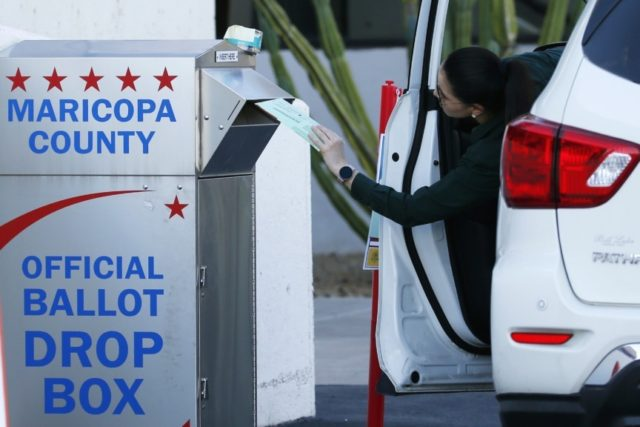 A voter drops off a ballot for the Arizona Democratic presidential preference election Tuesday, March 17, 2020, in Phoenix. (AP Photo/Ross D. Franklin)