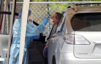 "A medical worker tests a person for the coronavirus at a drive-through facility primarily for first responders and medical personnel in San Antonio, Tuesday, March 17, 2020. Texas Gov. Greg Abbott said, ""This is not a time to panic. It's not as if we have never been through this before. …"