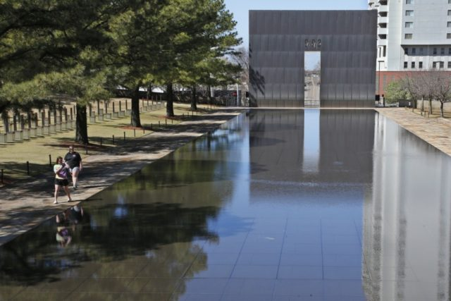 Visitors walk next to the reflecting pool at the Oklahoma City National Memorial and Museum in Oklahoma City, Wednesday, March 18, 2020. The Oklahoma City National Memorial and Museum has announced that it will offer a recorded, one-hour television program in place of a live ceremony to mark the 25th …