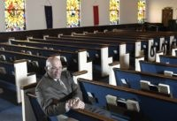 The Rev. Alvin J. Gwynn Sr., of Friendship Baptist Church in Baltimore, sits in his church's sanctuary, Thursday, March 19, 2020. He bucked the cancellation trend by holding services the previous Sunday. But attendance was down by about 50%, and Gwynn said the day's offering netted about $5,000 compared to …