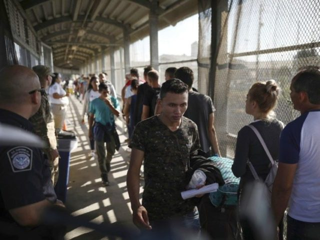 In this Aug. 2, 2019, file photo, migrants return to Mexico as other migrants line up on their way to request asylum in the U.S., at the foot of the Puerta Mexico bridge in Matamoros, Mexico, that crosses into Brownsville, Texas. One by one, asylum-seekers from El Salvador and Honduras …