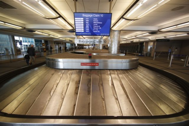 In this March 20, 2020 file photo, an empty baggage carousel spins in Denver International Airport as travelers deal with the spread of the coronavirus in Denver. Airline service in the United States is teetering on the brink of collapse, with near-empty planes and coronavirus-caused outbreaks that have left some …