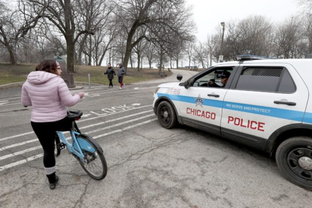 In this March 26, 2020, file photo, a Chicago police officer notifies a cyclist that the trails in Promontory Park, along Lake Michigan, are closed in an effort to limit the spread of COVID-19 infections, in Chicago. Chicago Mayor Lori Lightfoot's decision to shut down the trails along Lake Michigan …