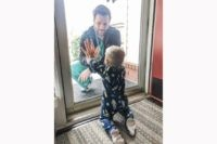 In this photo posted on Facebook, Wednesday, March 25, 2020, by Alyssa Burks, her husband, Dr. Jared Burks, sees his 1-year-old son crawl for the first time, as he touches a glass door from the outside while their son Zeke touches it from the inside of their Jonesboro, Ark. Home. …