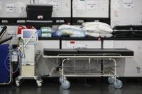 This Monday, March 23, 2020, file photo shows medical supplies and a stretcher displayed before a news conference at the Jacob Javits Center in New York. Health care workers are dreading the prospect of deciding which patients would get a ventilator that could save their lives. (AP Photo/John Minchillo, Fle)
