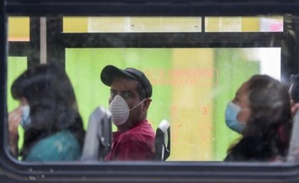 """Commuters wear masks as they ride a bus, to prevent the spread of the new coronavirus in Mexico City, Tuesday, March 31, 2020. Mexico's government has broadened its shutdown of """"non essential activities,"""" and prohibited gatherings of more than 50 people as a way to help slow down the spread …"""