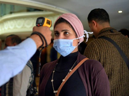 A woman wearing a protective health mask has her body temperature measured at on a touristic river boat in Egypt's southern city of Luxor on March 8, 2020, amidst efforts to detect possible COVID-19 coronavirus cases. - Egypt's health ministry said the 45 detected cases would be quarantined even though …