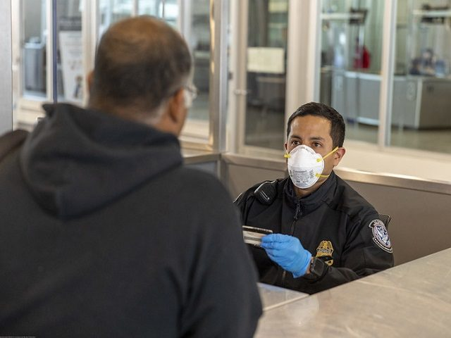 CBP officer at San Ydidro Port of Entry interviews a traveler while wearing PPE. (File Photo: U.S. Customs and Border Protection/Mani Albrecht)