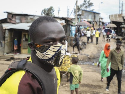 A boda-boda, or motorcycle taxi, driver wears a makeshift mask made from a local fabric known as Kitenge as he looks for customers in the Kibera neighbourhood of Nairobi, Kenya Friday, March 20, 2020. For most people, the new coronavirus causes only mild or moderate symptoms such as fever and …
