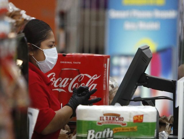 Amid social distancing during the Covid-19 outbreak, a cashier wears a mask while working behind a clear barrier between her and a customer at El Rancho grocery store in Dallas, Thursday, March 26, 2020. For most people, the new coronavirus causes mild or moderate symptoms, such as fever and cough …