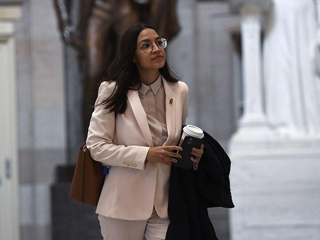 Rep. Alexandria Ocasio-Cortez, D-N.Y., walks Capitol Hill in Washington, Friday, March 27, 2020. (AP Photo/Susan Walsh)