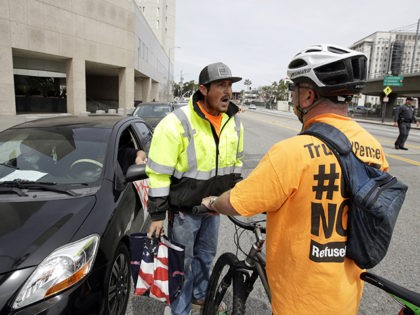 Demonstrators argue opposing views during a protest outside of the Edward R. Roybal Federal Building Tuesday, March 31, 2020, in Los Angeles. Demonstrators across California coordinated efforts in a car-based protest to demand the release of immigrants in California detention centers over concerns with the COVID-19 pandemic. (AP Photo/Marcio Jose …