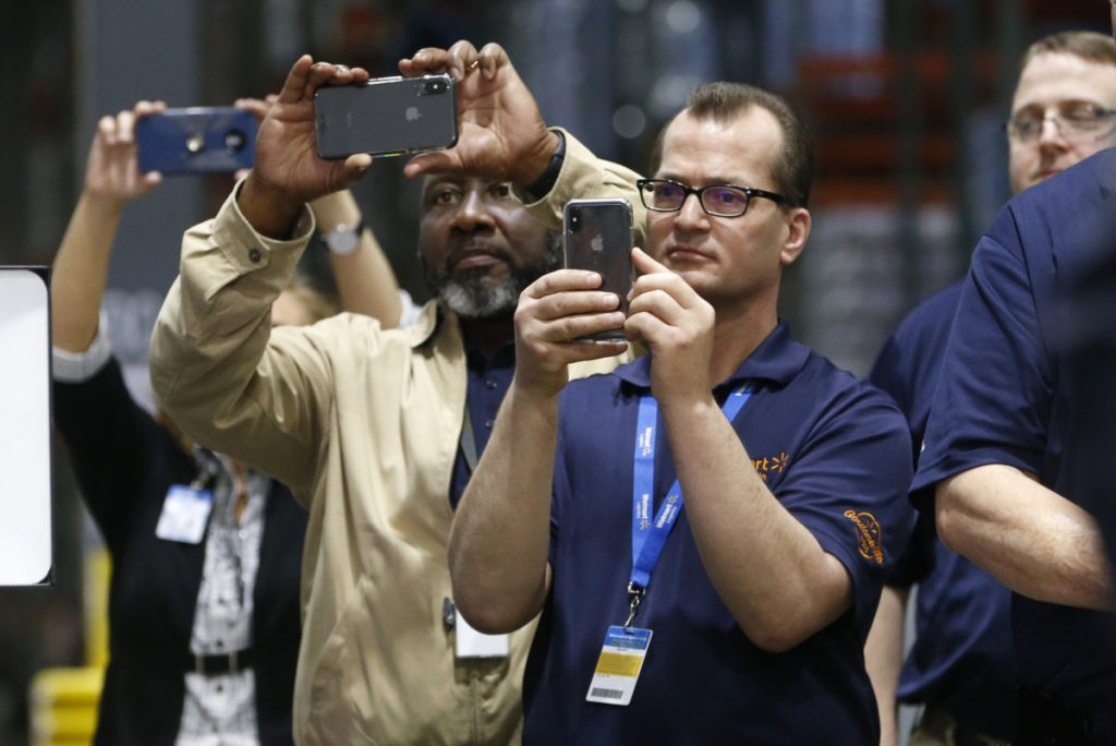 Walmart Distribution Center workers take photos of Vice President Mike Pence, as he tours the Center Wednesday, April 1, 2020, in Gordonsville, Va. (AP Photo/Steve Helber)
