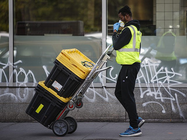 A delivery worker adjusts his mask while wearing personal protective equipment due to COVID-19 and coronavirus concerns before making a pickup outside a Whole Foods Market, Wednesday, April 1, 2020, in New York. The new coronavirus causes mild or moderate symptoms for most people, but for some, especially older adults …