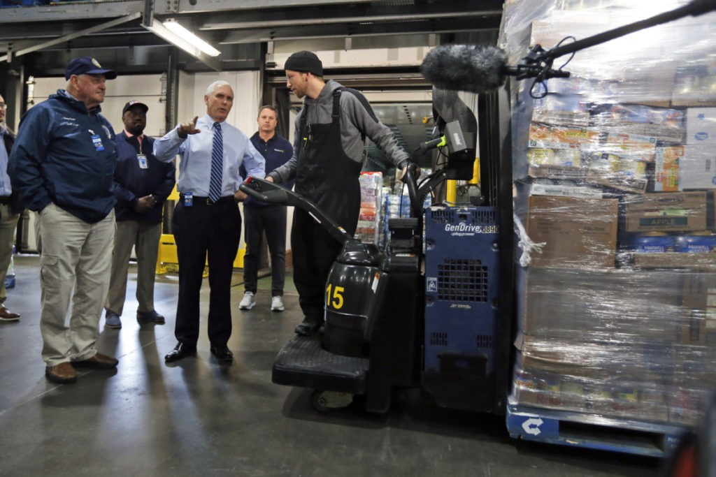 Vice President Mike Pence, second from right, talks with a worker preparing to load a truck as Agriculture Secretary Sunny Perdue, left, looks on at a Walmart Distribution Center Wednesday, April 1, 2020, in Gordonsville, Va. (AP Photo/Steve Helber)