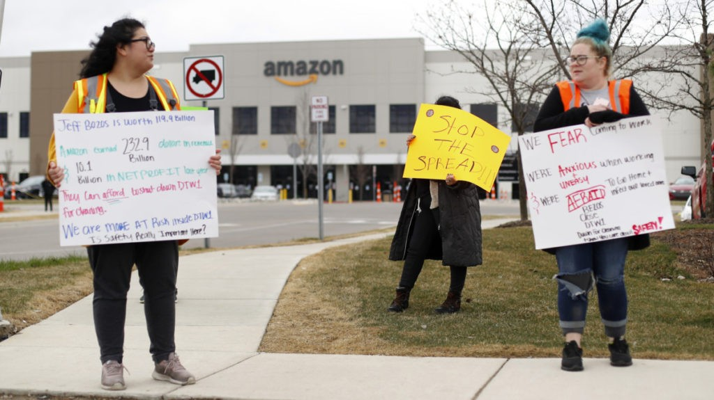 Employee's Breana Avelar, left, and Tonya Ramsay, right, hold signs outside the Amazon DTW1 fulfillment center in Romulus, Mich., Wednesday, April 1, 2020. Employees and family members are protesting in response what they say is the company's failure to protect the health of its employees amid the new coronavirus COVID-19 outbreak. (AP Photo/Paul Sancya)