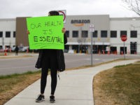 A family member of an employee holds a sign outside the Amazon DTW1 fulfillment center in Romulus, Mich., Wednesday, April 1, 2020. Employees and family members are protesting in response to what they say is the company's failure to protect the health of its employees amid the new coronavirus COVID-19 …