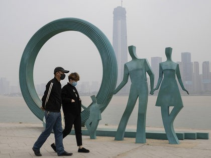 Residents wearing masks against the coronavirus walk past sculpture along the banks of the Yangtze River in Wuhan in central China's Hubei province on Friday, April 3, 2020. (AP Photo/Ng Han Guan)