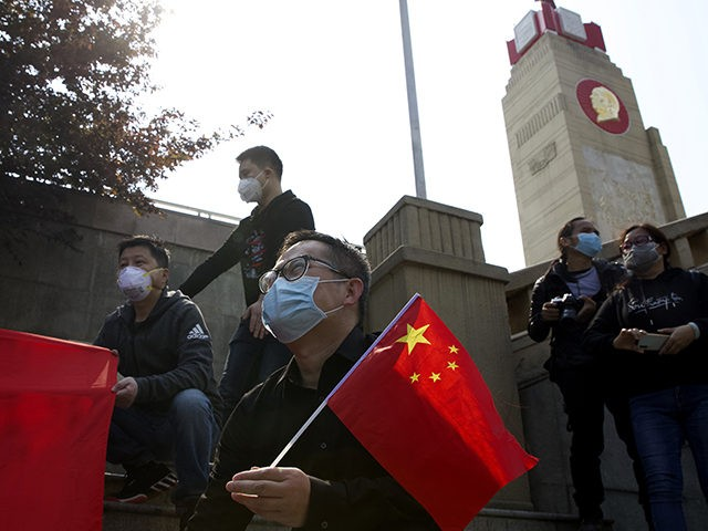 People hold Chinese flags as they gather outside of a park where an official memorial was held for victims of coronavirus in Wuhan in central China's Hubei Province, Saturday, April 4, 2020. With air raid sirens wailing and flags at half-mast, China held a three-minute nationwide moment of reflection to …