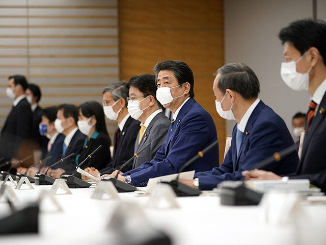 Japanese Prime Minister Shinzo Abe, center, declares a state of emergency during a meeting of the task force against the coronavirus at the his official residence in Tokyo, Tuesday, April 7, 2020. Abe declared a state of emergency for Tokyo and six other prefectures to ramp up defenses against the …