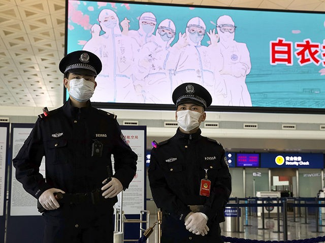 Police officers wearing face masks to protect against the spread of new coronavirus stand guard at Wuhan Tianhe International Airport in Wuhan in central China's Hubei Province, Wednesday, April 8, 2020. Within hours of China lifting an 11-week lockdown on the central city of Wuhan early Wednesday, tens of thousands …