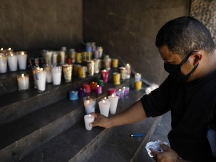 Juan Pablo Rosa Victorin, 34, wears a protective face mask as he lights candles on behalf of his wife, who is hospitalized for reasons unrelated to COVID-19, at the Basilica of Our Lady of Guadalupe, where the principal part of the church is closed to the public to prevent the …