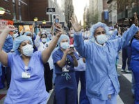 Nurses and medical workers react as police officers and pedestrians cheer them outside Lenox Hill Hospital Wednesday, April 15, 2020, in New York. (AP Photo/Frank Franklin II)