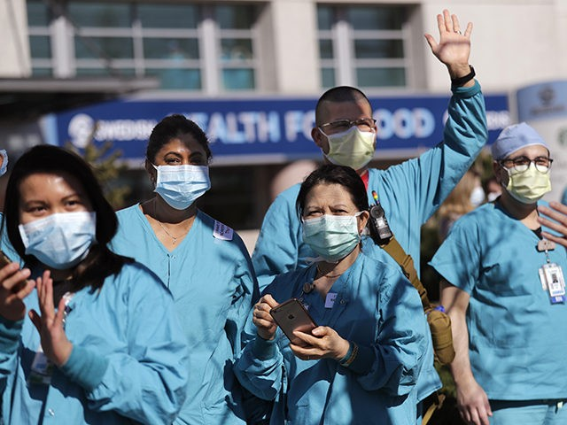 Swedish Medical Center health care workers look on as first responders gathered outside the hospital in support of them in their work against the coronavirus outbreak Thursday, April 16, 2020, in Seattle. First responders across King County planned to stand outside of 15 hospitals in a show of appreciation for …