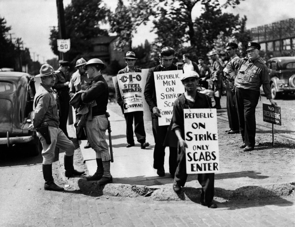 """No trespassing"" says sign on which officer at right is leaning, so these striking workers perform their picketing duties on the sidewalk in front of the Republic Steel Corporation's plant in Youngstown, Ohio, July 1, 1937, where the ""back-to-work"" movement gained impetus under the protection of the Ohio National Guard, left. (AP Photo)"