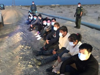 Border Patrol agents wearing masks provide PPE to apprehended migrants. (File Photo: U.S. Border Patrol)
