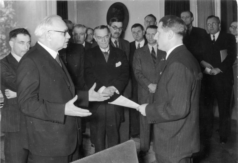 The Third Reich Health Leader Leonardo Conti (right) holds the Report of the International Katyn Commission, 4 May 1943, in front of Dr. Ferenc Orsós from the University of Budapest. Centre, Professor Louis Speleers of the Ghent University in Belgium. Eduard Miloslavić, Croatian professor of pathology, is the 4th person from left