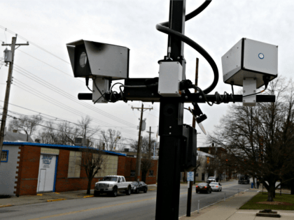 This Wednesday, Jan. 16, 2013 file photo shows a pair of traffic cameras aimed on Vine Street, in Elmwood Place, Ohio. People suing the Cincinnati-area village over speeding tickets generated by a camera system want a judge to rule in their favor without trial, filing a motion for summary judgement …