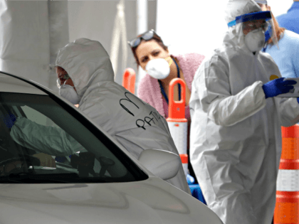 A medical worker, center left, uses a swab to administer a test to an unidentified person for the coronavirus at a drive-through testing site in a parking at Gillette Stadium, Sunday, April 5, 2020, in Foxborough, Mass. The site, which opened Sunday, is designated specifically for police officers, firefighters and …