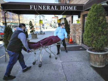 Employees deliver a body to a funeral home