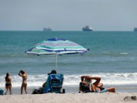 Despite a stay at home policy due to the coronavirus in Florida, beach goers enjoy the sun as cruise ships, without passengers, float offshore Saturday, April 4, 2020, in Cape Canaveral, Fla. Although some of the county beaches remained open, with out parking, many beach goers remained at home. (AP …