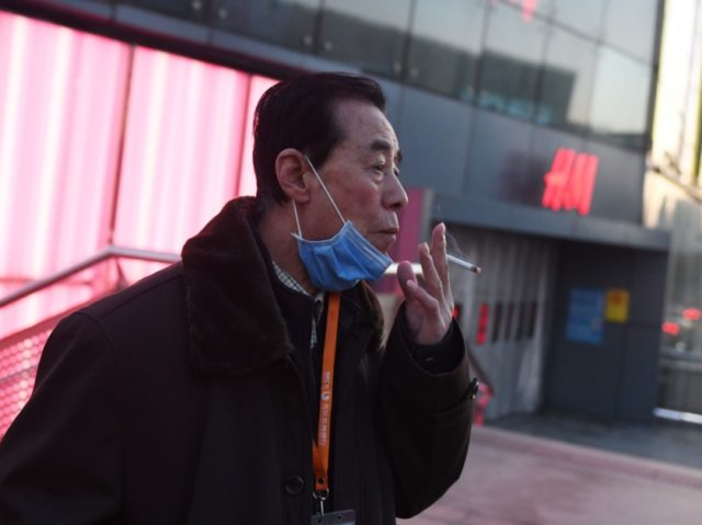 A man lowers his face mask to smoke a cigarette in Beijing on February 17, 2020. - The death toll from China's COVID-19 coronavirus epidemic jumped to 1,770 after 105 more people died, the National Health Commission said on February 17. More than 70,500 have now been infected nationwide by …