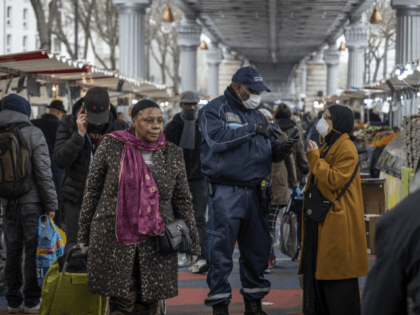 PARIS, FRANCE - MARCH 18: Shoppers visit a food market in a popular district of the 18th Arrondissement, where police advise the crowds on measures taken by the government to combat the spread of COVID-19 on March 18, 2020 in Paris, France. France imposed a nationwide lockdown to control the …