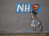 Graffiti depicting the badge of the fictional super heros Superman and Superwoman, and the logo of Britain's National Health Service (NHS) above street art of a nurse, are pictured on a wall in Pontefract, northern England on April 3, 2020, as life in Britain continues during the nationwide lockdown to …