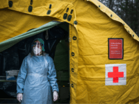 A medical staffer at Sophiahemmet hospital stands at the entrance of a tent for testing and receiving potential coronavirus COVID-19 patients on April 7, 2020 in Stockholm. (Photo by Jonathan NACKSTRAND / AFP) (Photo by JONATHAN NACKSTRAND/AFP via Getty Images)