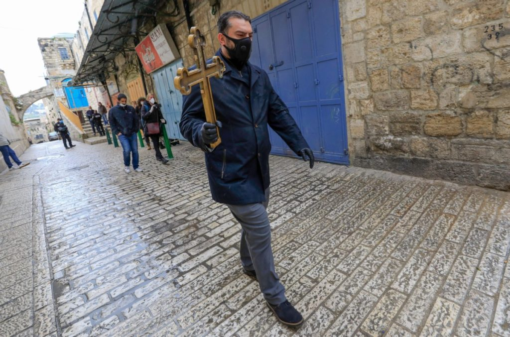 A Christian pilgrim wearing protective gear amid the COVID-19 outbreak, holds a cross while making his way alone in the Procession of the Way of the Cross along the Via Dolorosa, to mark Good Friday in Jerusalem on April 10, 2020. - All cultural sites in the Holy Land are shuttered, regardless of their religious affiliation, as authorities seek to forestall the spread of the deadly respiratory disease, which will prevent Christians from congregating for the Easter service, this coming Sunday for Catholic worshippers, then a week later on April 19 for Orthodox Easter. (Photo by Emmanuel DUNAND / AFP) (Photo by EMMANUEL DUNAND/AFP via Getty Images)