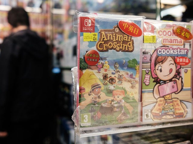 A copy of Nintendo computer game Animal Crossing: New Horizons (C) is displayed in a shopping mall as a customer browses other games in Hong Kong on April 10, 2020. (Photo by Anthony WALLACE / AFP) (Photo by ANTHONY WALLACE/AFP via Getty Images)