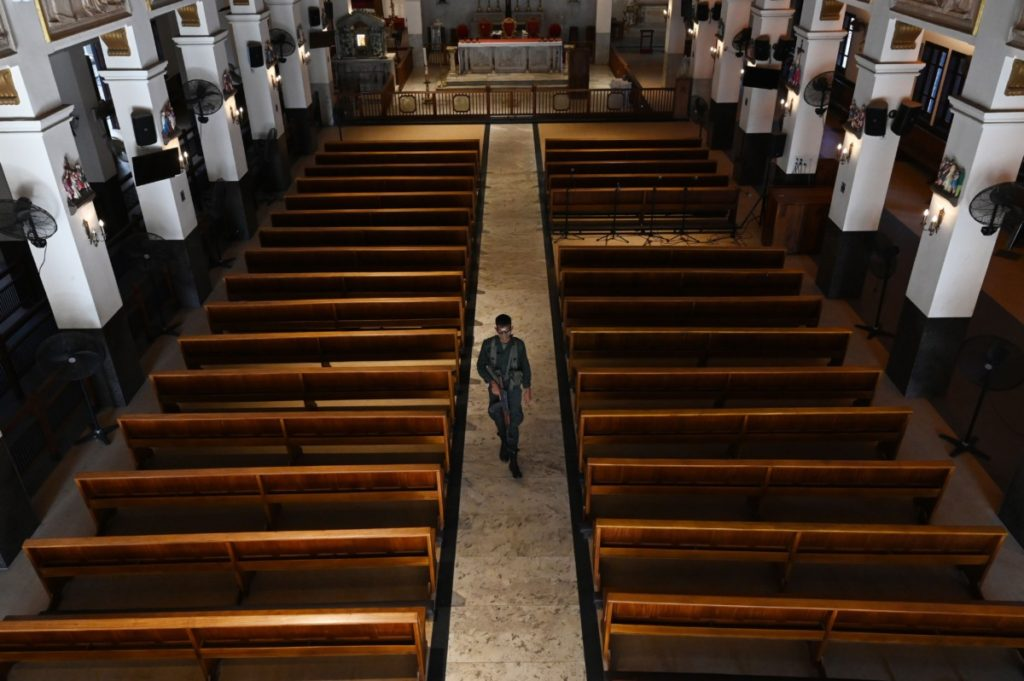 """TOPSHOT - A Sri Lankan army soldier walks inside the empty St Anthony's church on the first anniversary of the 2019 Easter Sunday bombings in Colombo on April 12, 2020, as the country remains under an indefinite curfew as part of measures to contain the spread of the COVID-19 coronavirus in the country. - Sri Lanka's Roman Catholic Church said on April 12 it had forgiven the suicide bombers behind the attacks that killed at least 279 people last Easter. Cardinal Malcolm Ranjith told an Easter mass -- broadcast from a TV studio because of the coronavirus pandemic -- that """"we offered love to the enemies who tried to destroy us"""". (Photo by LAKRUWAN WANNIARACHCHI / AFP) (Photo by LAKRUWAN WANNIARACHCHI/AFP via Getty Images)"""