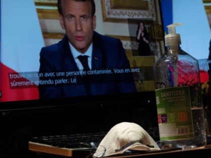 French President Emmanuel Macron is seen on a monitor in Paris, next to a face mask and a bottle of hand sanitiser, as he speaks from the Elysee Palace during a televised address to the nation on April 13, 2020, on the 28th day of a lockdown in France aimed …