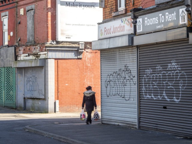 A woman carries shopping past closed shops in Leeds city centre, West Yorkshire on April 14, 2020, as life in Britain continues during the nationwide lockdown to combat the novel coronavirus COVID-19 pandemic. - Britain's economy could shrink by an unprecedented 13 percent this year in the case of a …