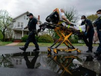 (FILES) In this file photo taken on April 13, 2020, firefighters and paramedics with Anne Arundel County Fire Department transport a patient experiencing COVID-19 symptoms in Glen Burnie, Maryland. (Photo by Alex Edelman / AFP) / RESTRICTED TO EDITORIAL USE (Photo by ALEX EDELMAN/AFP via Getty Images)