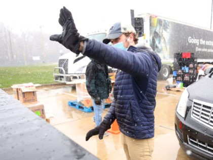 OAK PARK, MICHIGAN - APRIL 15: Sean Furtol of Beverly Hills and a Forgotten Harvest volunteer waves after loading eggs into a car on April 15, 2020 in Detroit, Michigan. The organization distributes food throughout the metro area, which has seen an uptick in demand due to the COVID-19 pandemic. …