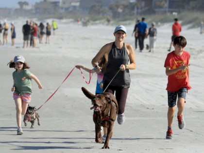 People run on the beach on April 17, 2020 in Jacksonville Beach, Florida. Jacksonville Mayor Lenny Curry announced Thursday that Duval County's beaches would open at 5 p.m. but only for restricted hours and can only be used for swimming, running, surfing, walking, biking, fishing, and taking care of pets. …