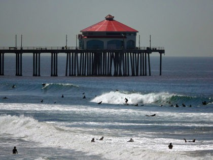 HUNTINGTON BEACH, CA - APRIL 22: Surfers ride waves in front of the Huntington Beach pier on the beach on April 22, 2020 in Huntington Beach, California. Southern California is expecting summer like weather over the next week as social distancing and beach closures continue due to the coronavirus (COVID-19). …